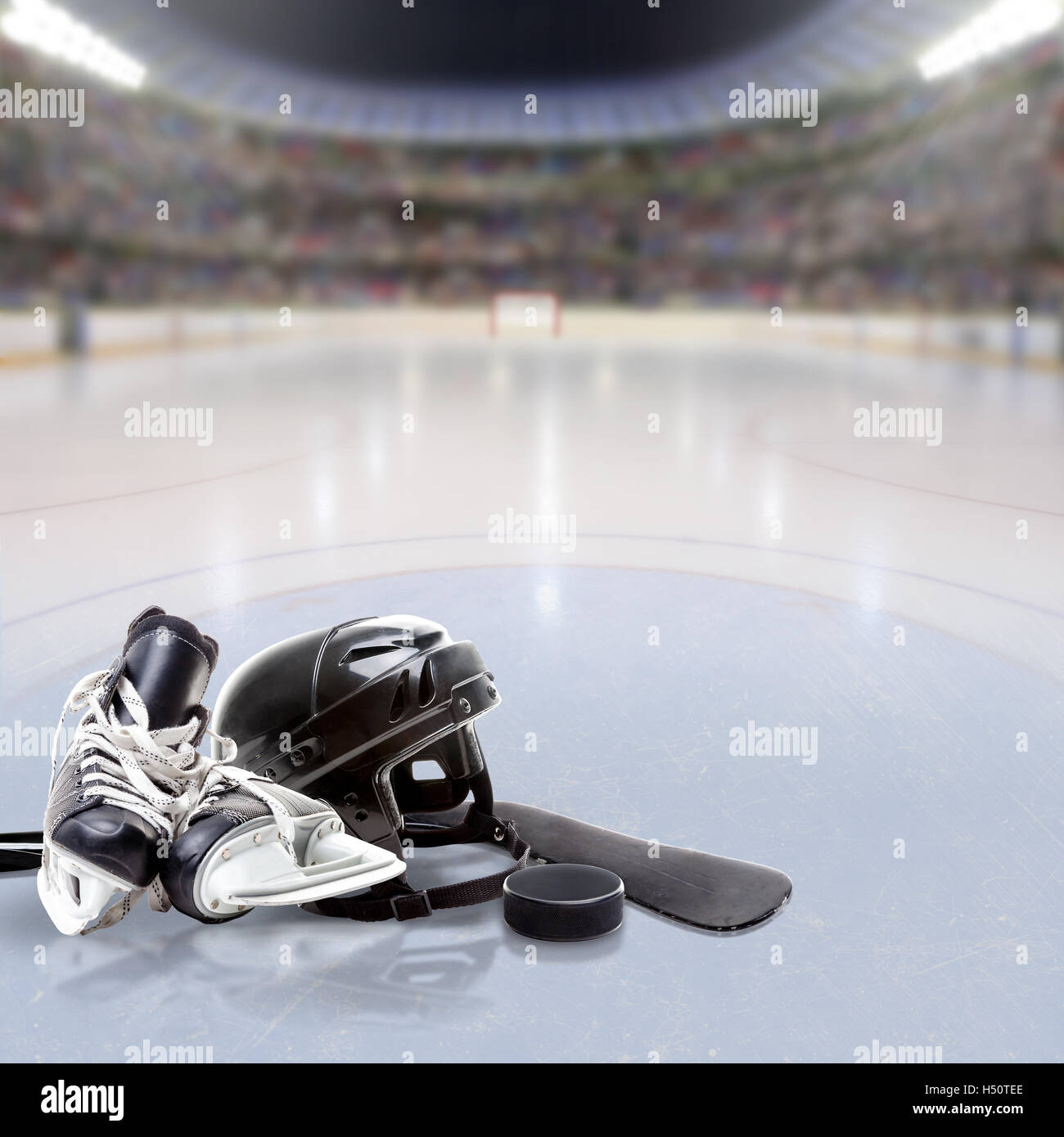 Hockey arena full of fans in the stands with helmet, skates, stick and puck on ice and copy space. Deliberate focus - Stock Image