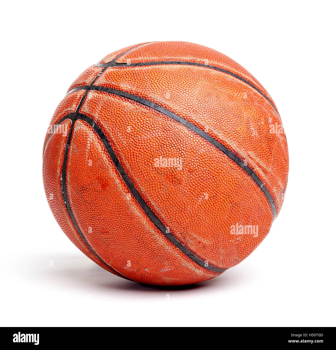 An old rugged and worn out basketball isolated on white background. - Stock Image