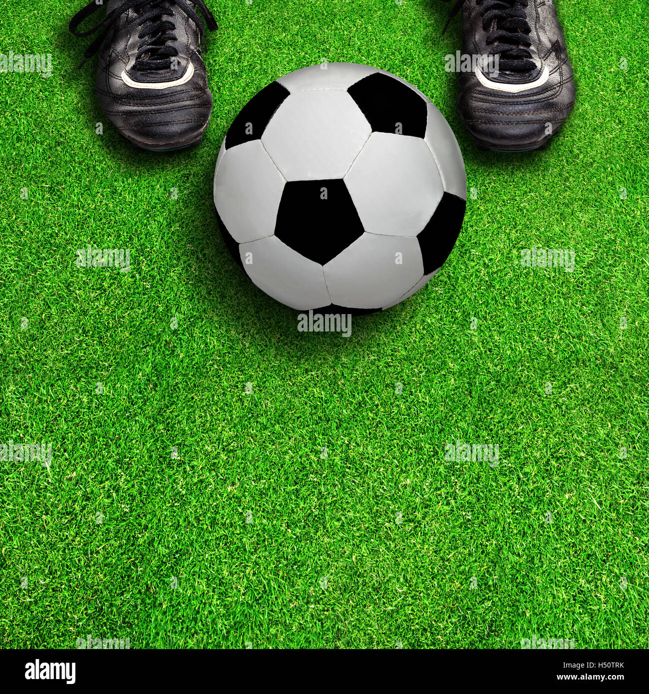 8ed624d04da Player standing on field showing soccer cleats with ball and copy space  below. - Stock