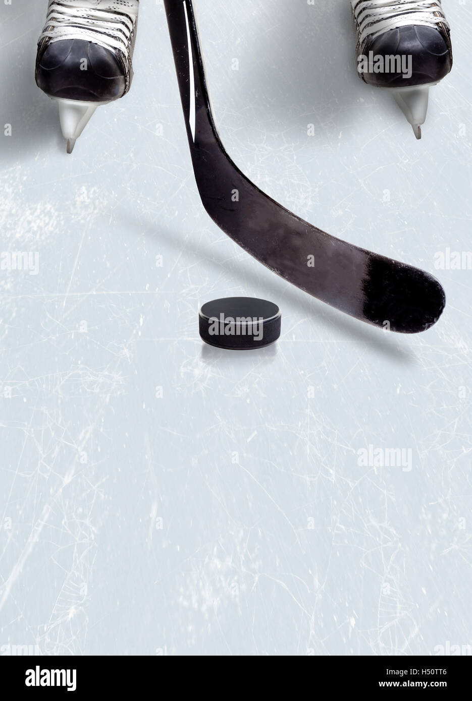 Hockey stick and puck on ice with a player's skates showing partically and copy space. Vertical orientation. - Stock Image