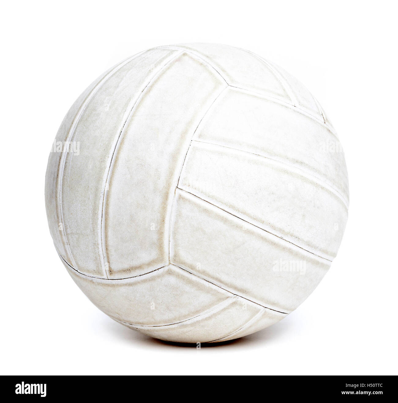 An old rugged and worn out volleyball isolated on white background. - Stock Image