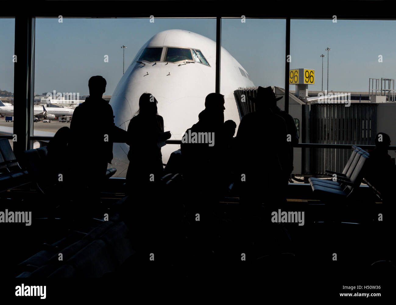 Silhouette of passengers waiting at the airport gate with the nose of an aircraft outside on the airport tarmac. - Stock Image