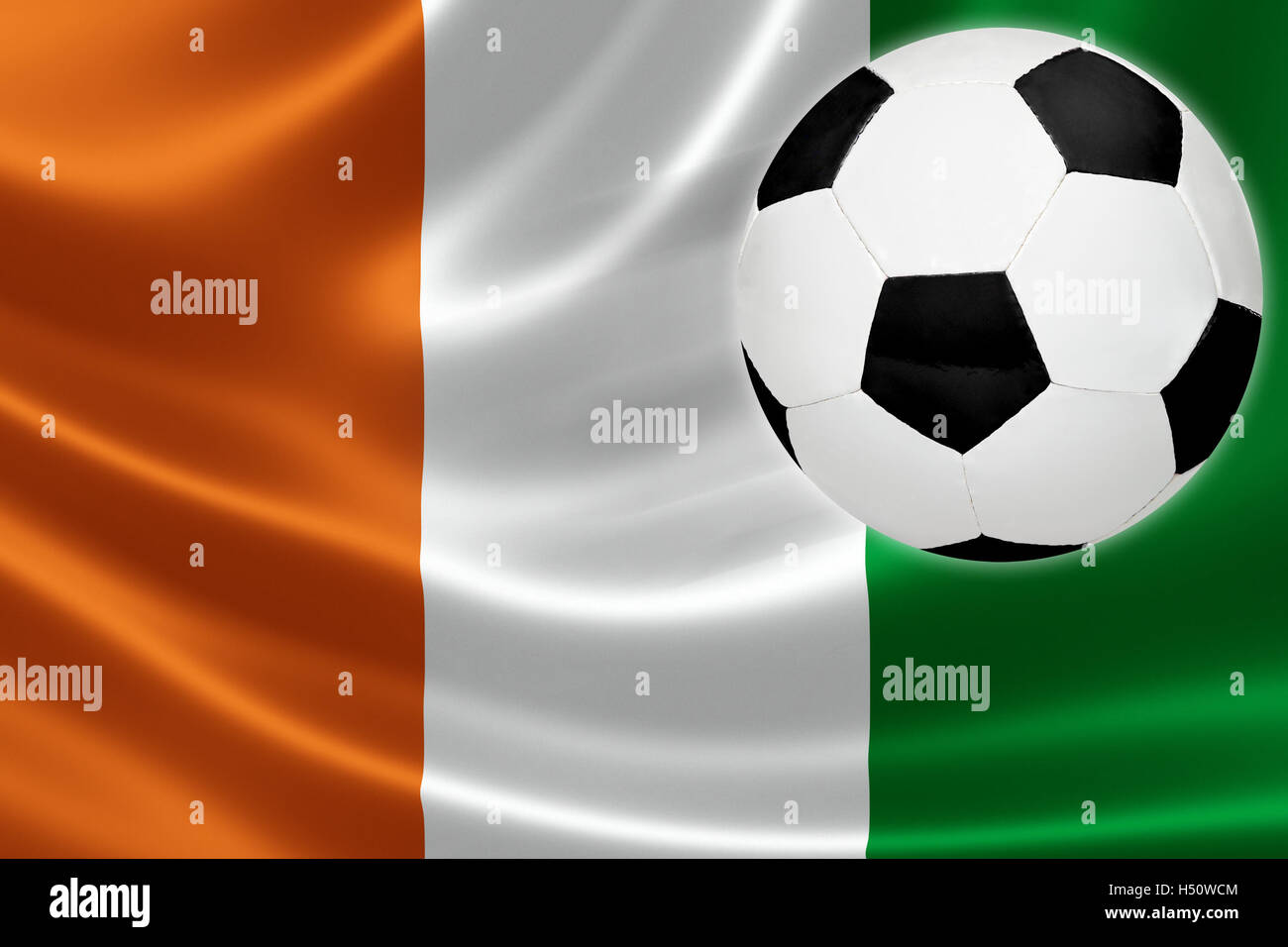 Ball streaks across the flag of Cote d'Ivoire, where soccer is a national passion. - Stock Image