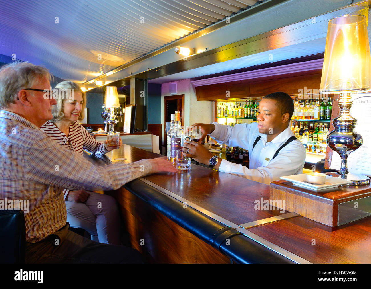 A couple sampling whisky at the Bascule Whisky, Wine & Cocktail Bar of Cape Grace Hotel. - Stock Image