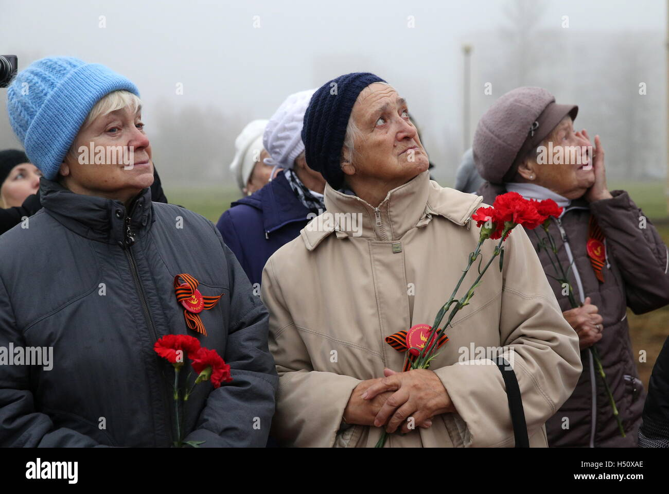 TIKHVIN, LENINGRAD REGION, RUSSIA - OCTOBER 14, 2016: People lay flowers at a war memorial unveiled to mark the - Stock Image