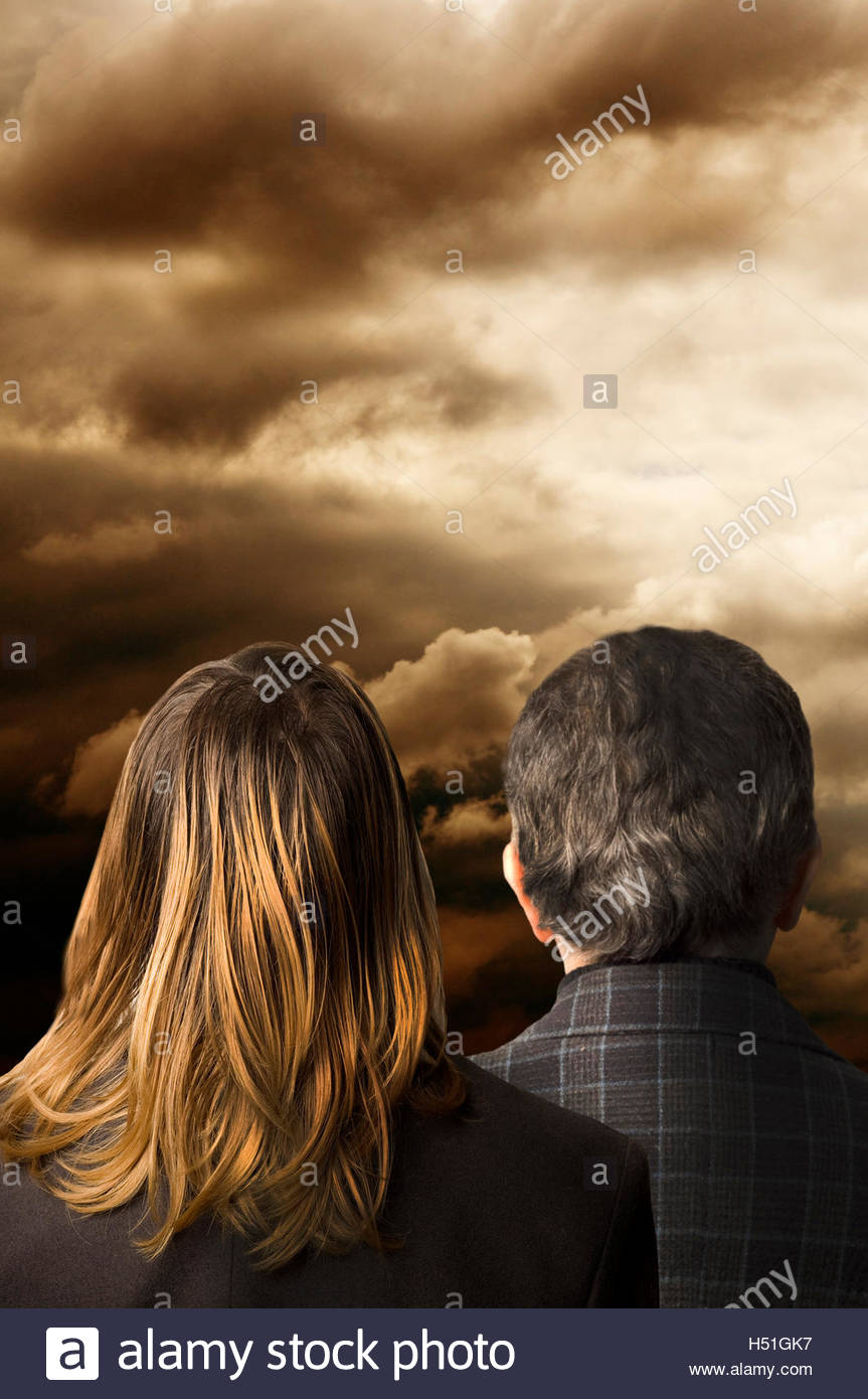 man and woman back, looking ahead at uncertain times - Stock Image