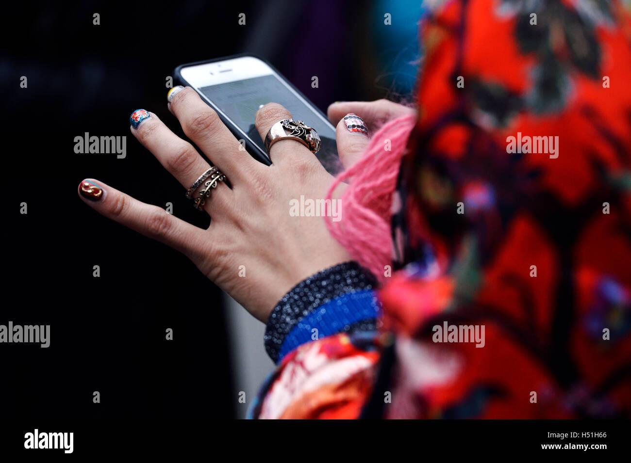 Woman using smartphone at Paris Fashion Week 2016 - Stock Image