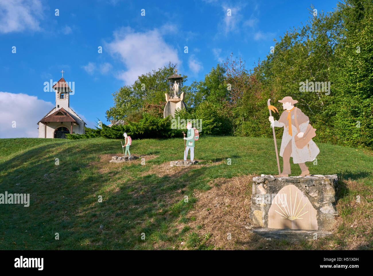 Pilgrim figures by Chapelle Saint-Romain on the Camino de Santiago above Jongieux-le-Haut. Savoie, France. - Stock Image