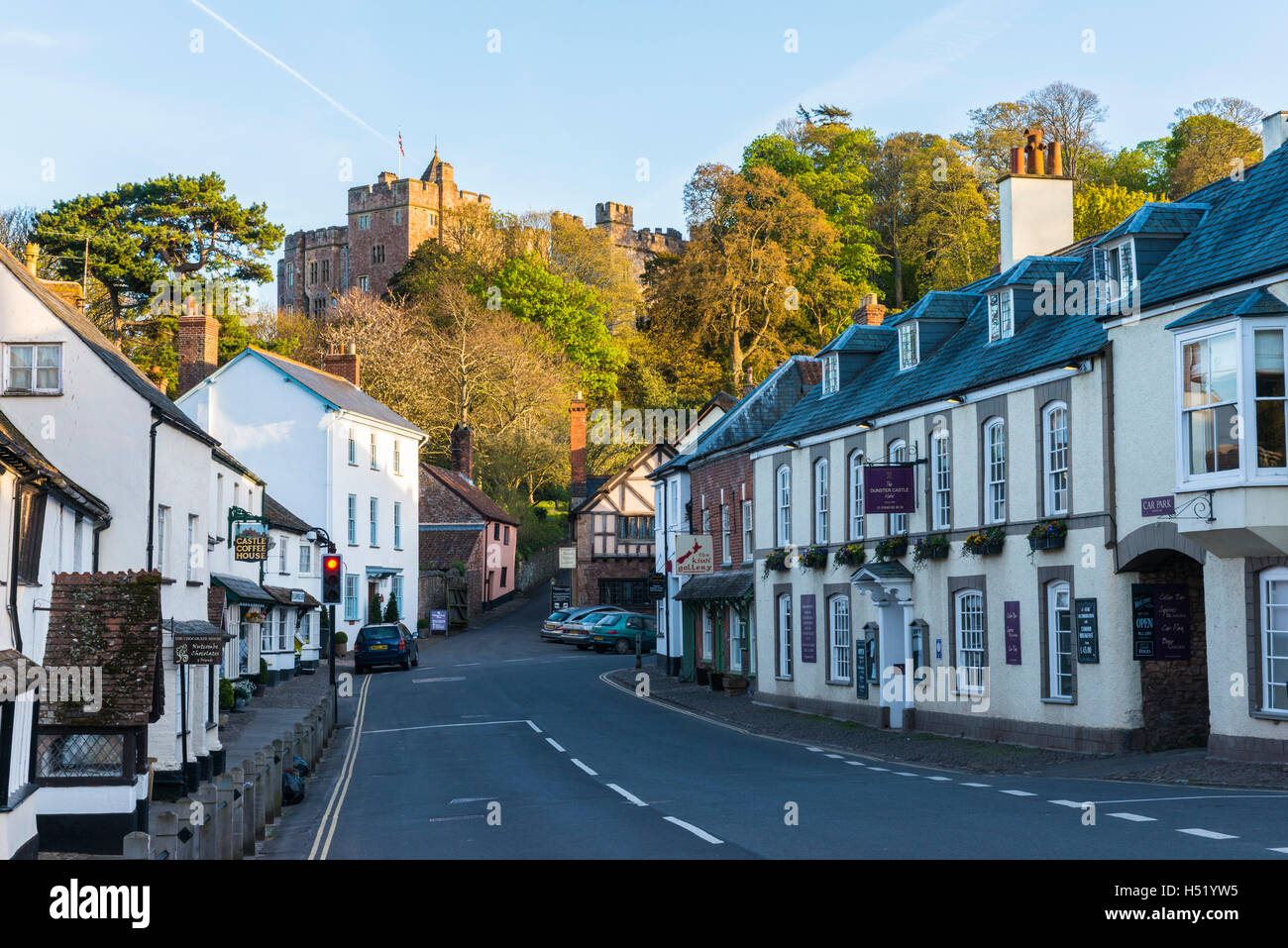 The picturesque village of Dunster in Somerset with the castle perched on the hill above the village framed by the Stock Photo