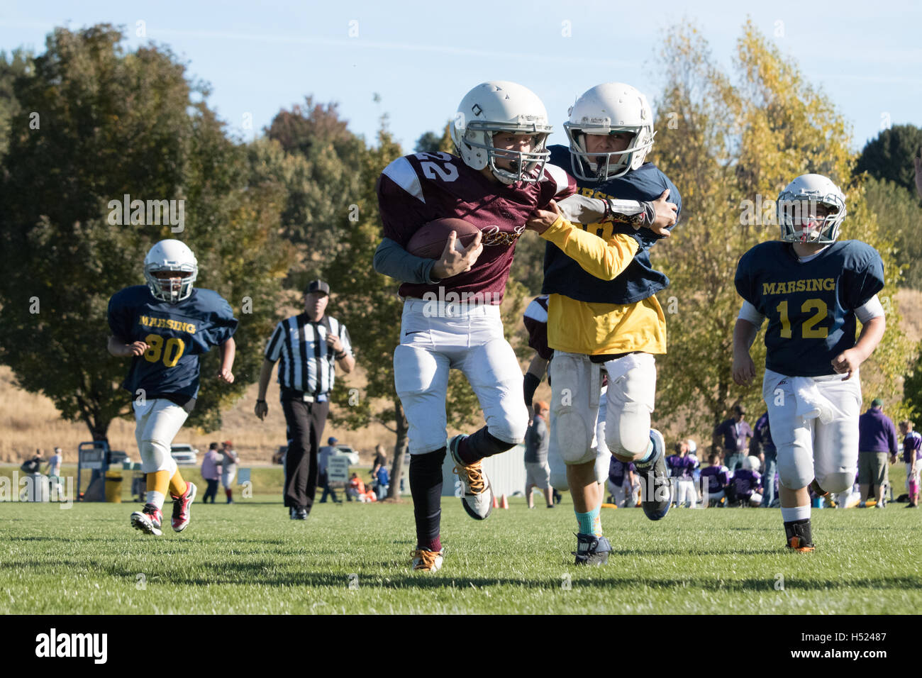 Youth football receiver runs the ball in for a touchdown. - Stock Image