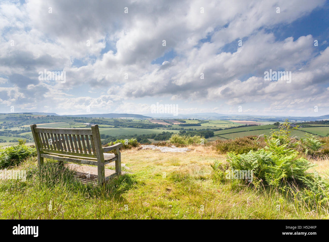 Wooden bench overlooking a wonderful view over the valley to the distant hills on a bright and cheery sunny day, Stock Photo