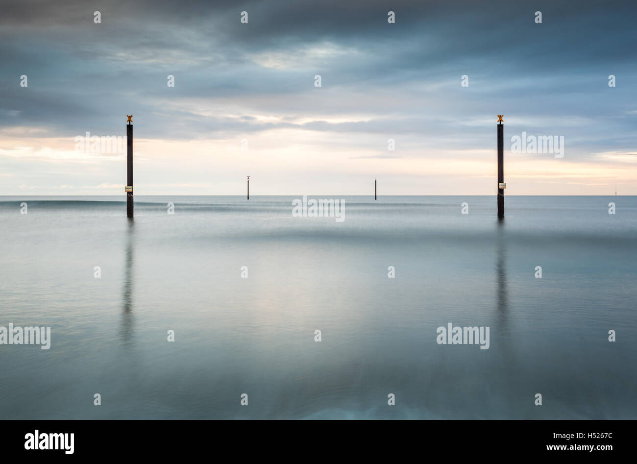 Navigation guide posts out at sea in the North Sea off the Northumberland coast, long exposure on an overcast day Stock Photo