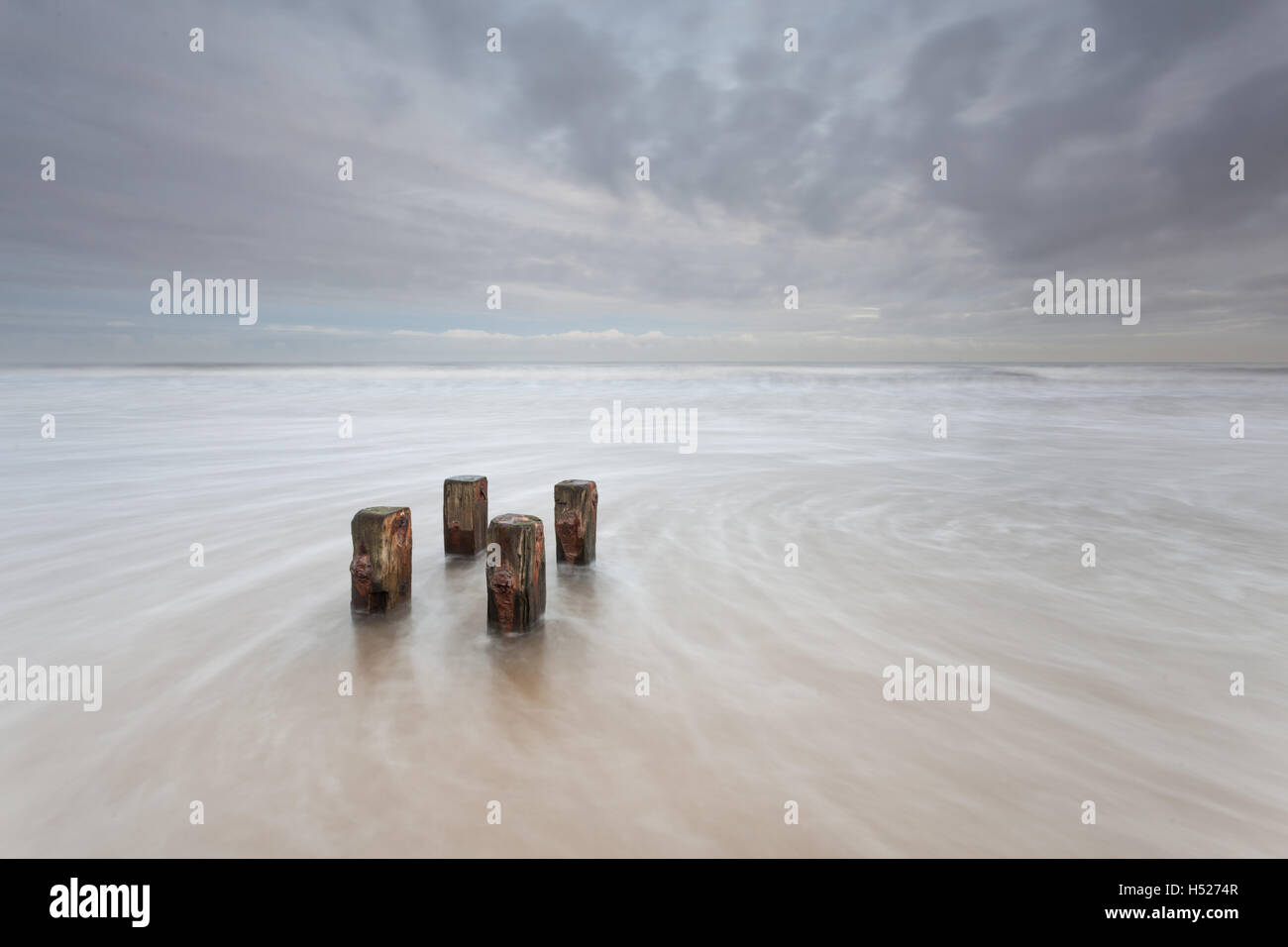 Wooden posts of an old groyne at the beach as the north sea rushes in at high tide on the Northumberland coast on - Stock Image