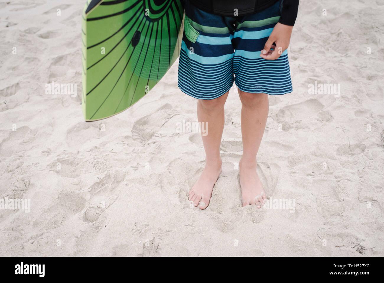 Boy on a sandy beach, wearing stripy blue swimming trunks, holding a bodyboard. - Stock Image