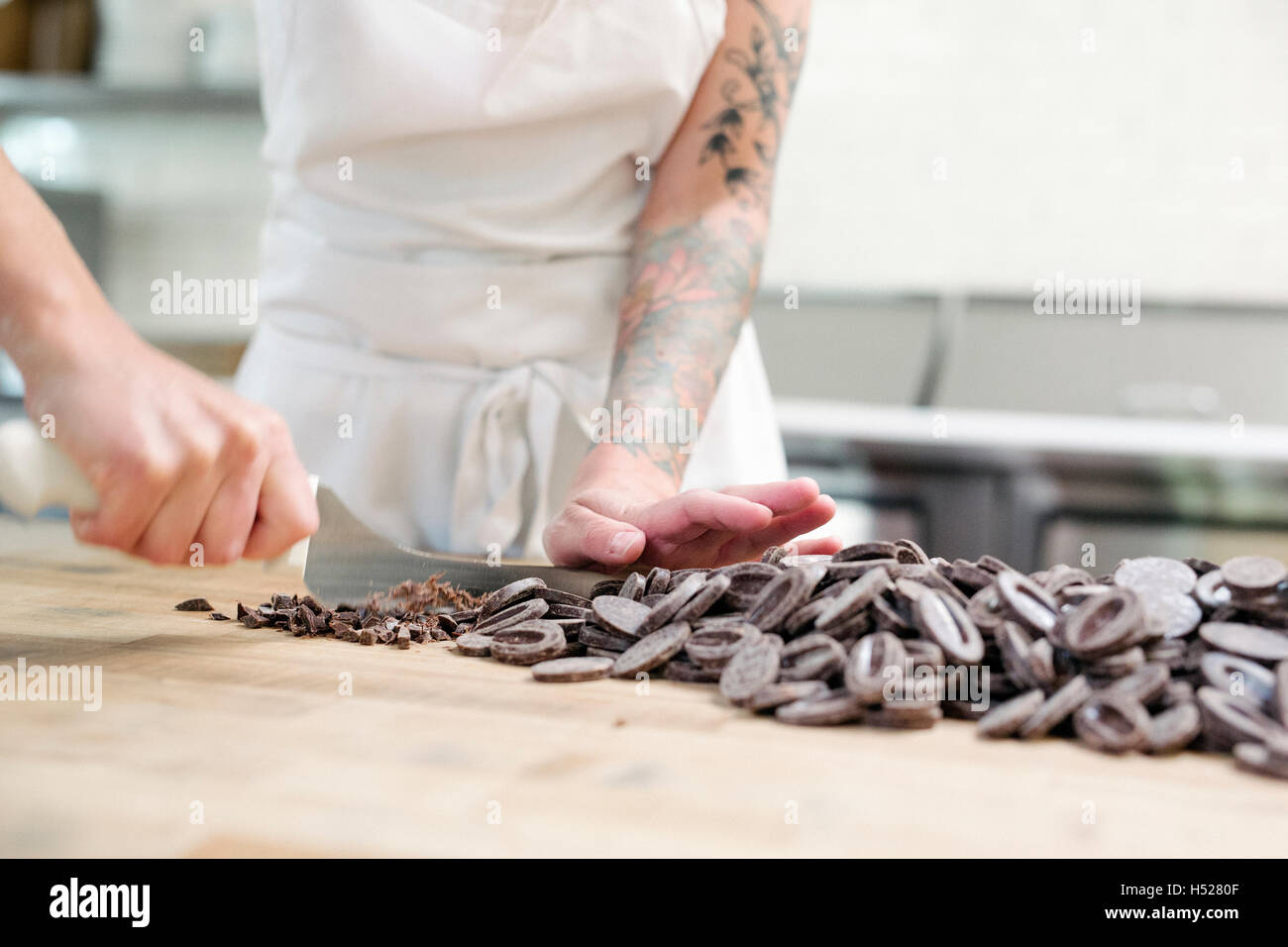 Close up of a woman wearing a white apron at a work counter in a bakery, chopping chocolate. - Stock Image