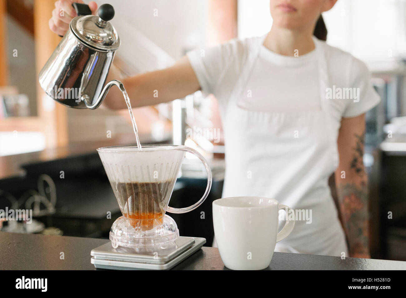 Woman wearing a white apron in a coffee shop, making filter coffee. - Stock Image
