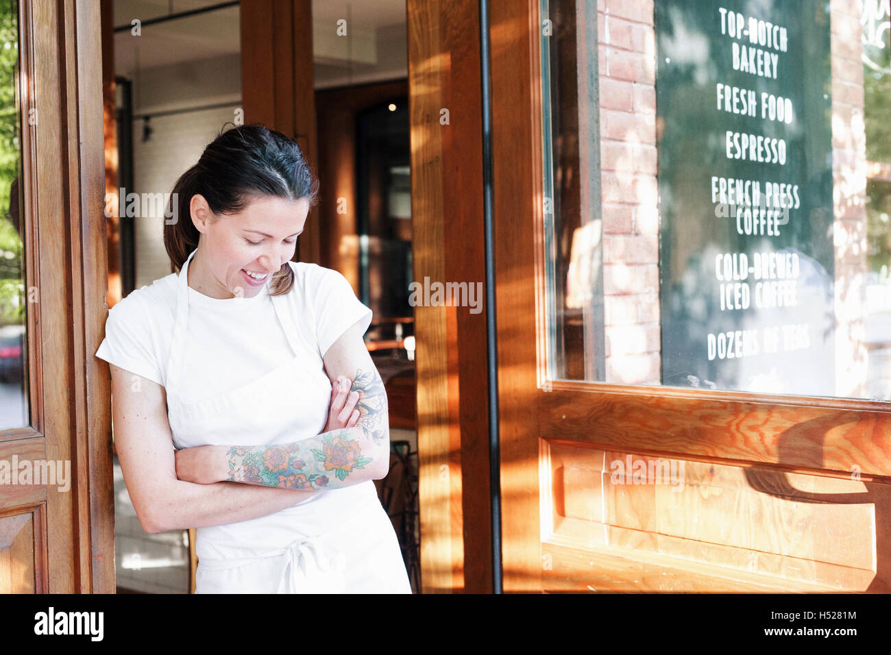 Portrait of a woman wearing a white apron with her arms crossed in a doorway, tattoos on her left arm. - Stock Image