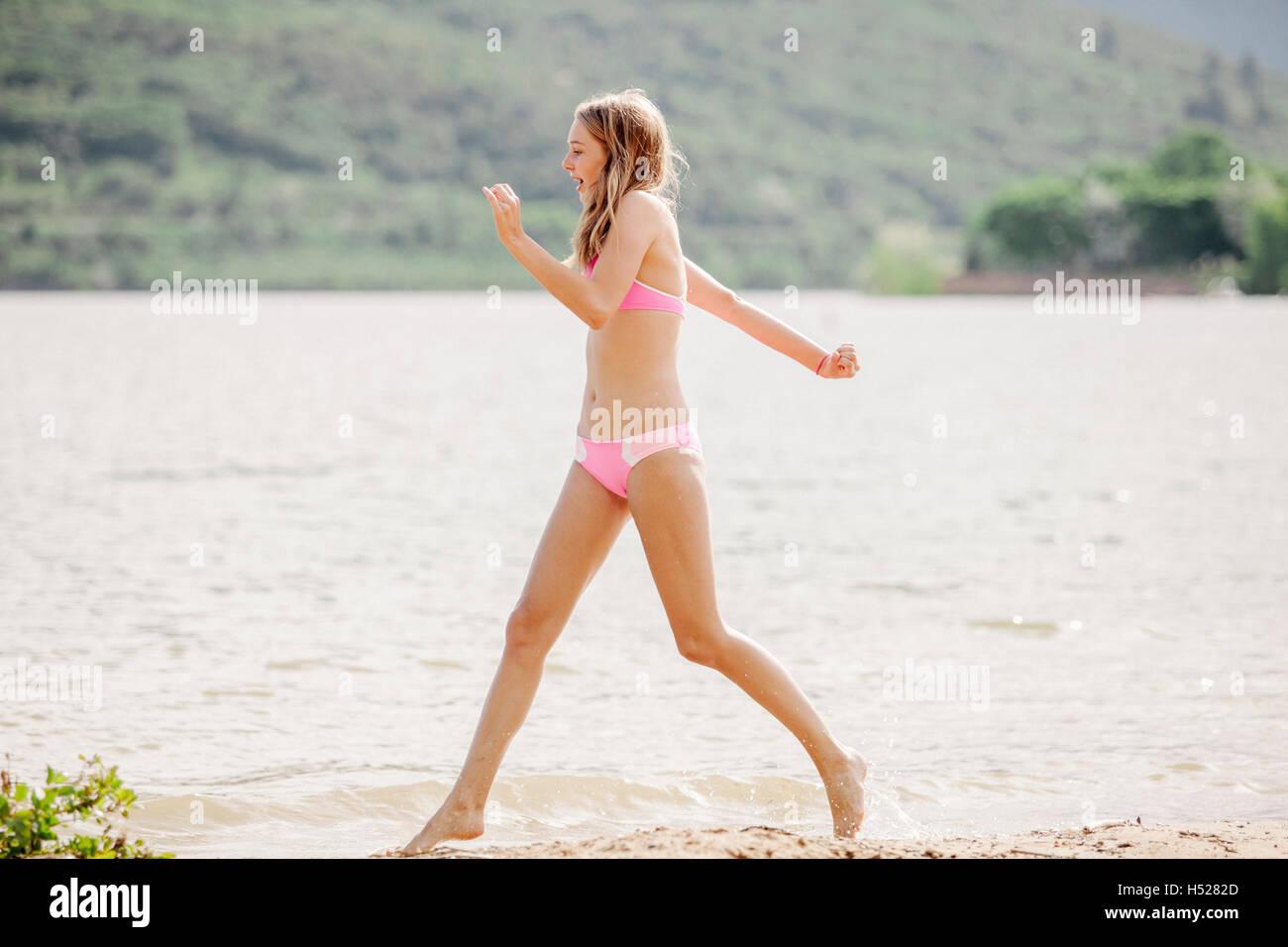 Teenage girls wearing a pink bikini running along a sandy ...