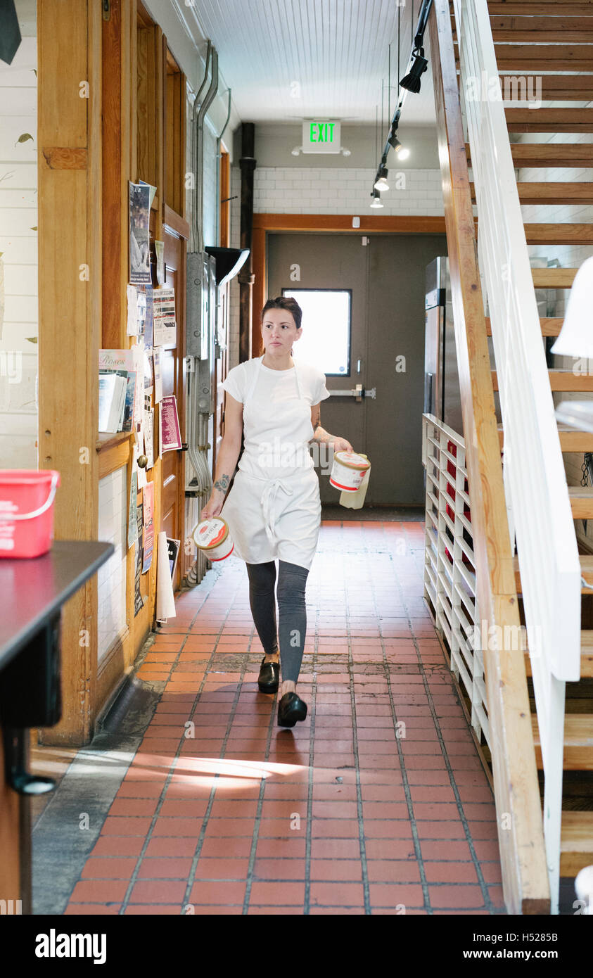 Woman wearing apron walking along a corridor, carrying two food containers. - Stock Image