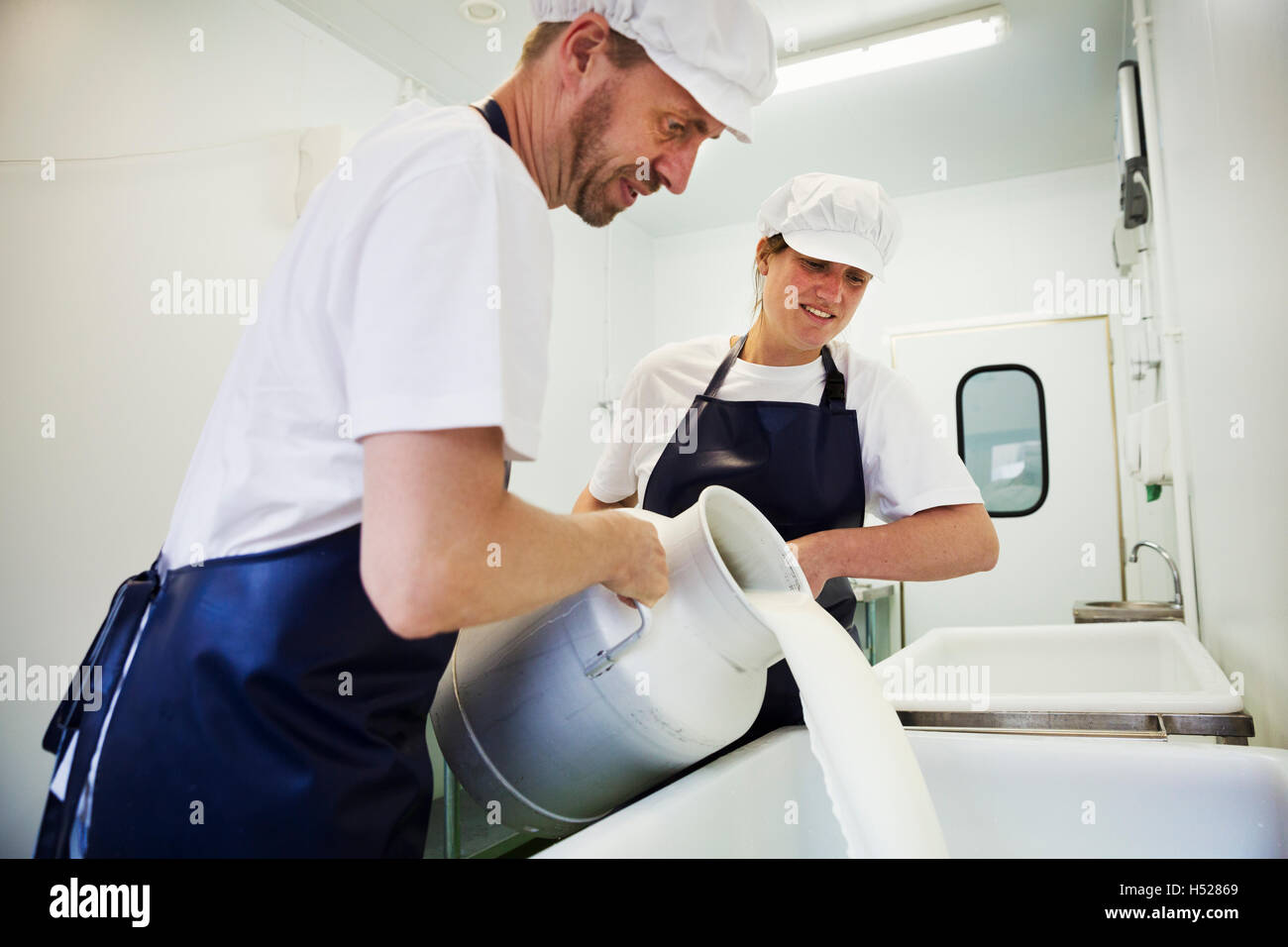 Man and woman  in a creamery, pouring goats milk from a churn, making goats cheese. - Stock Image