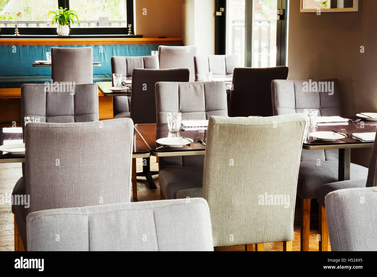 View of tables and grey upholstered chairs in a restaurant. - Stock Image