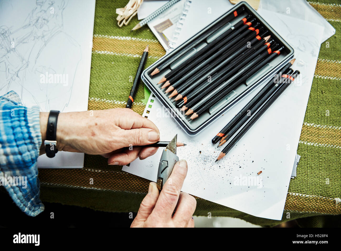 A person using a sharp blade, a craft knife, to sharpen lead pencils. Sketches on paper. - Stock Image