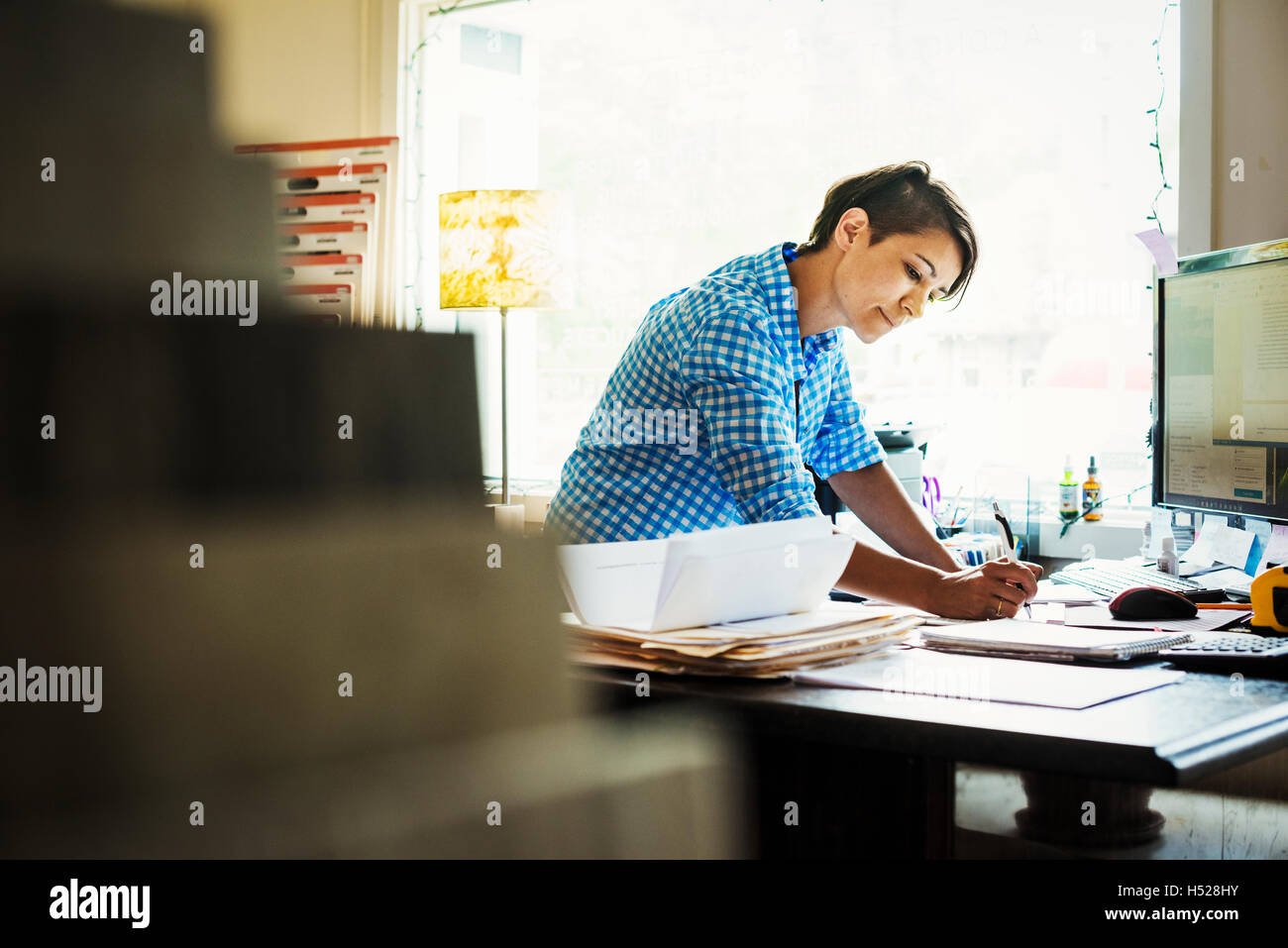 Woman working at a desk in interior design studio and accessories store. - Stock Image