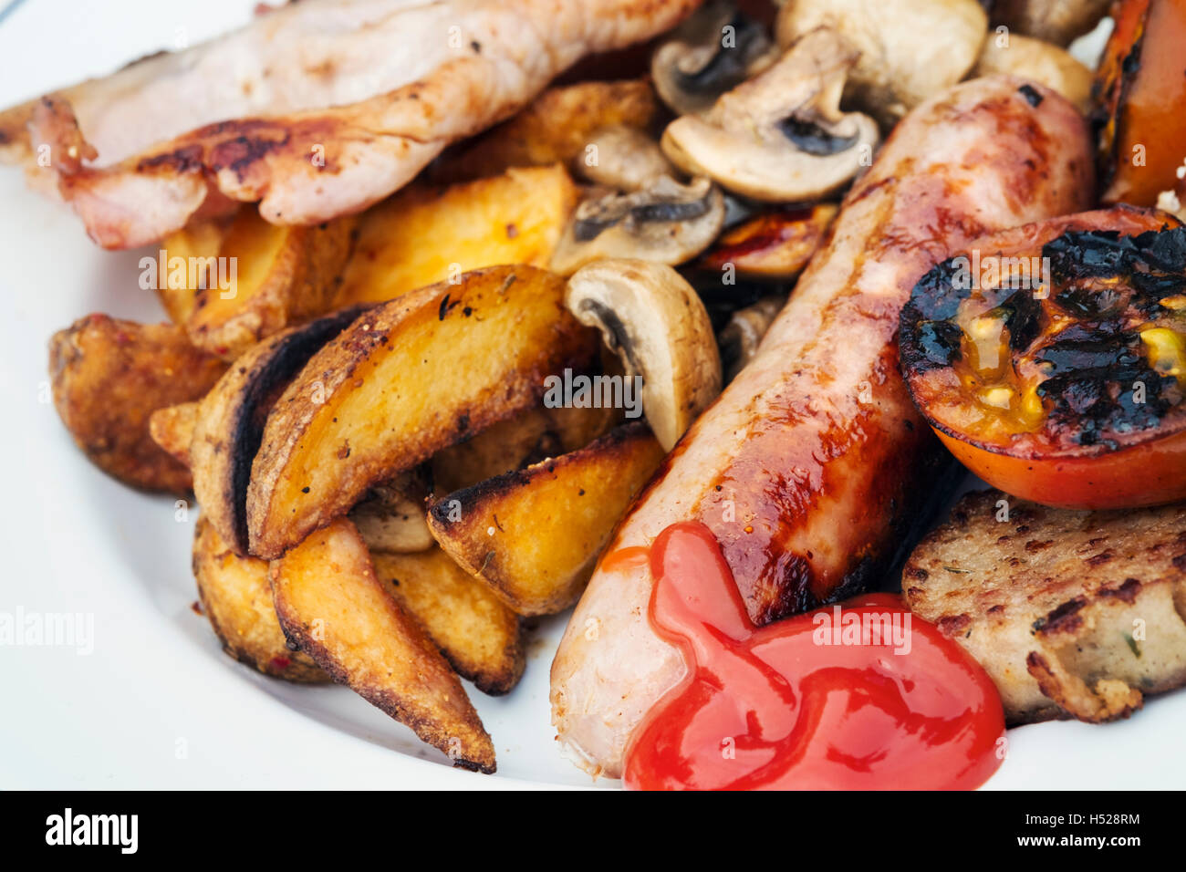 Close up of a plate of food, English Breakfast, bacon, mushrooms, sausage, grilled tomato, potatoes and tomato sauce. - Stock Image