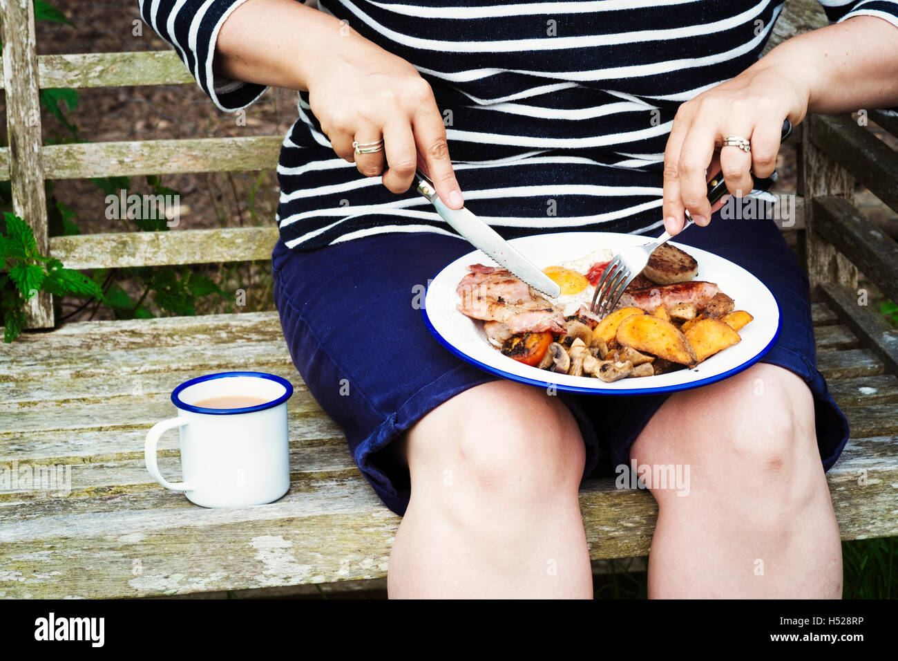 Woman sitting on a bench, eating from a plate of food balanced on her knees. - Stock Image