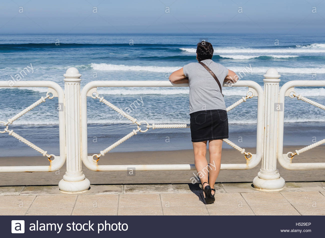 Short haired woman wearing miniskirt looking at the sea from the promenade - Stock Image