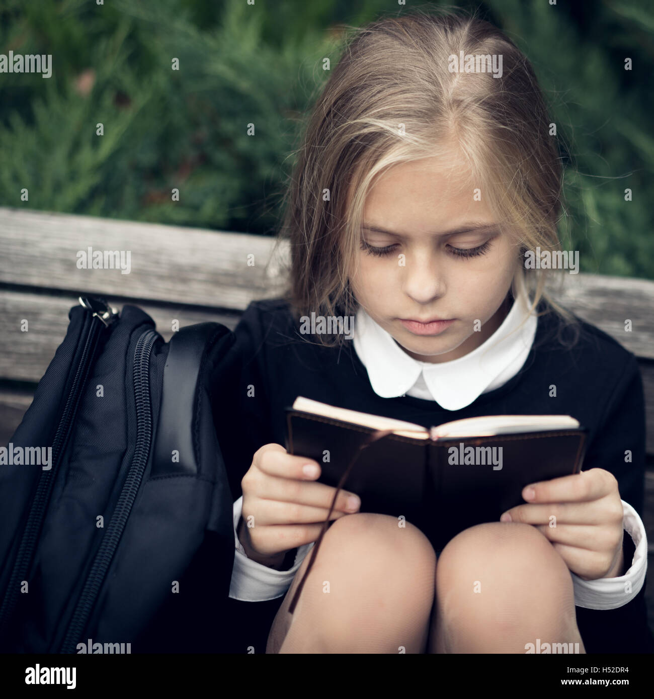 Beautiful blond girl in a school uniform sits on park bench and reading book. - Stock Image