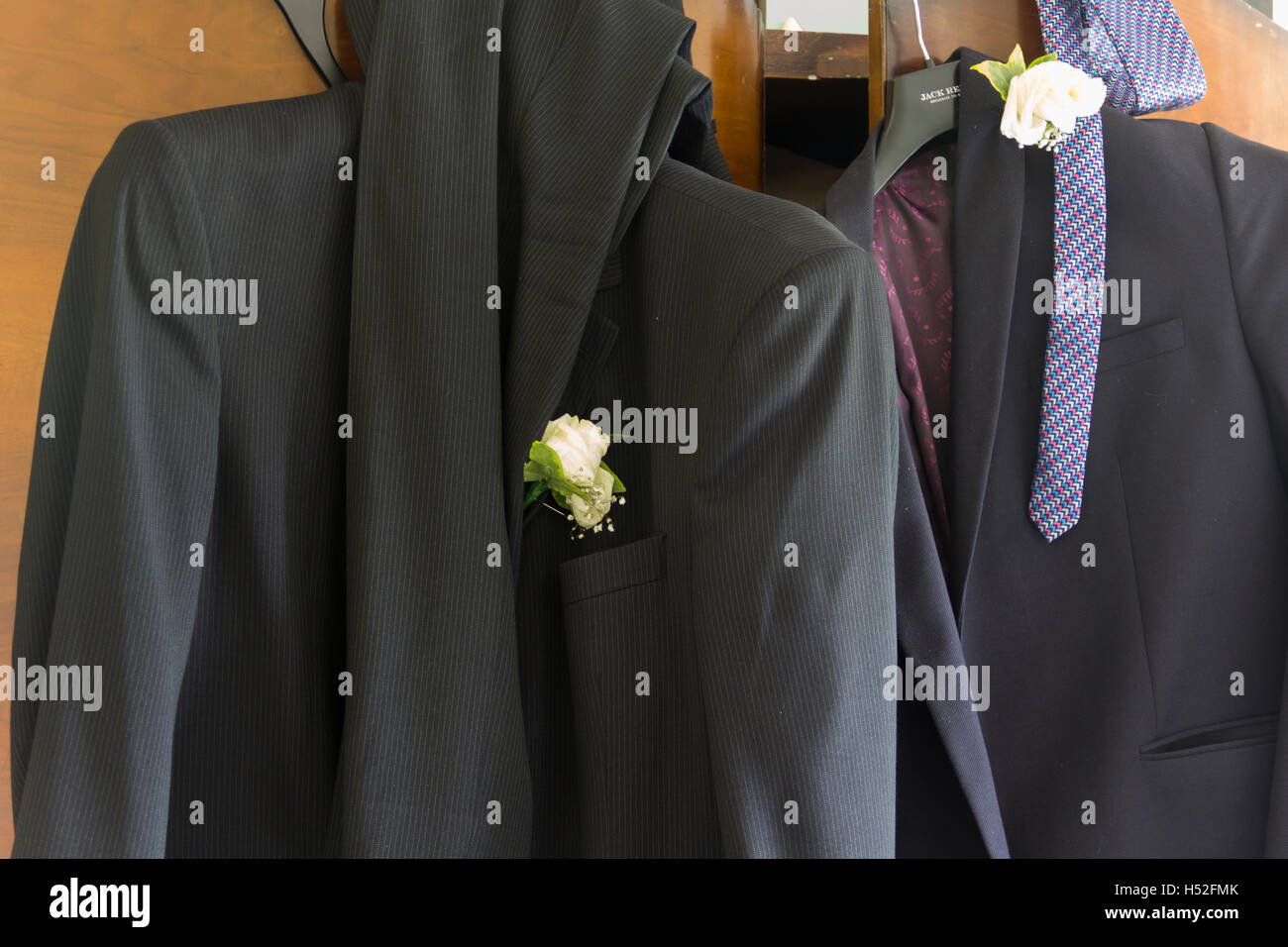 Two men's suits, worn by wedding guests, with white carnation buttonholes hung carelessly on a wardrobe door - Stock Image