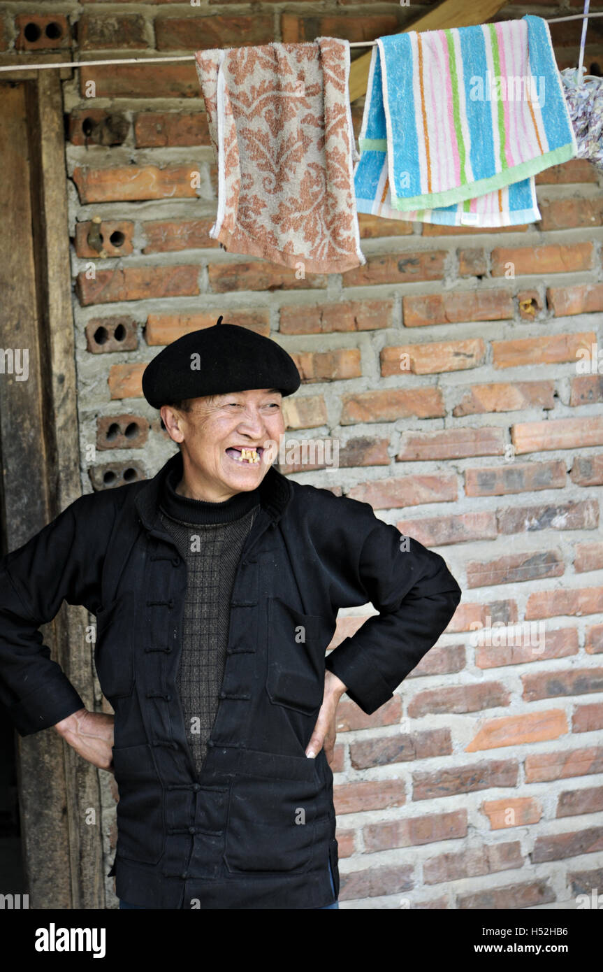 Woman with toothless smile outside her home in the province of Ha Giang, North Vietnam Stock Photo