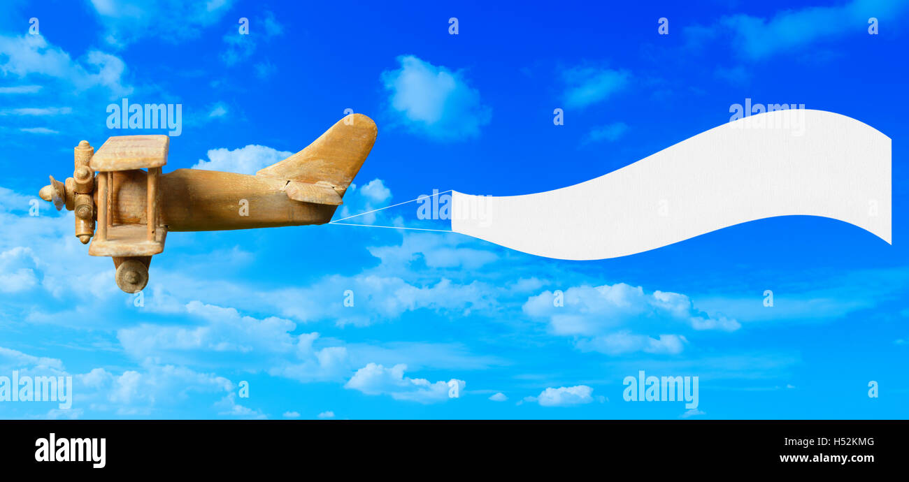Vintage Wooden Toy Plane Flying In Blue Sky Pulling A Blank White Banner Ready For Your