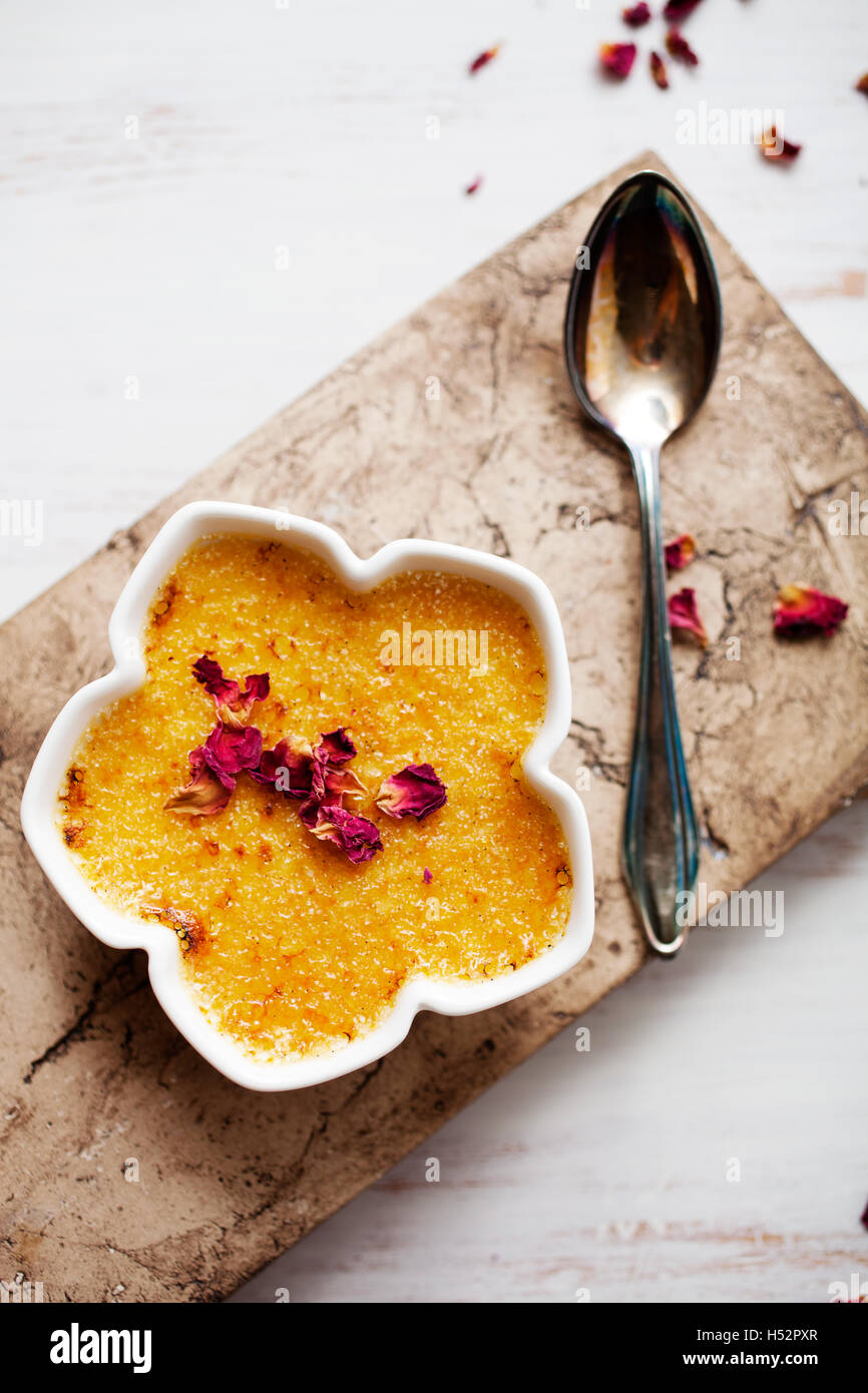 Homemade creme brulee with edble pink roses - Stock Image