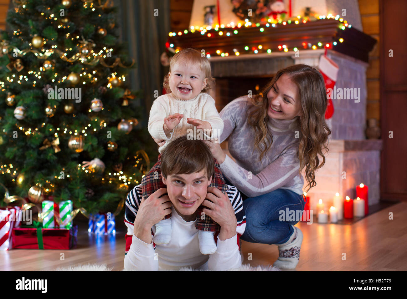 christmas, x-mas, family, people, happiness concept - happy parents playing with pretty baby boy - Stock Image