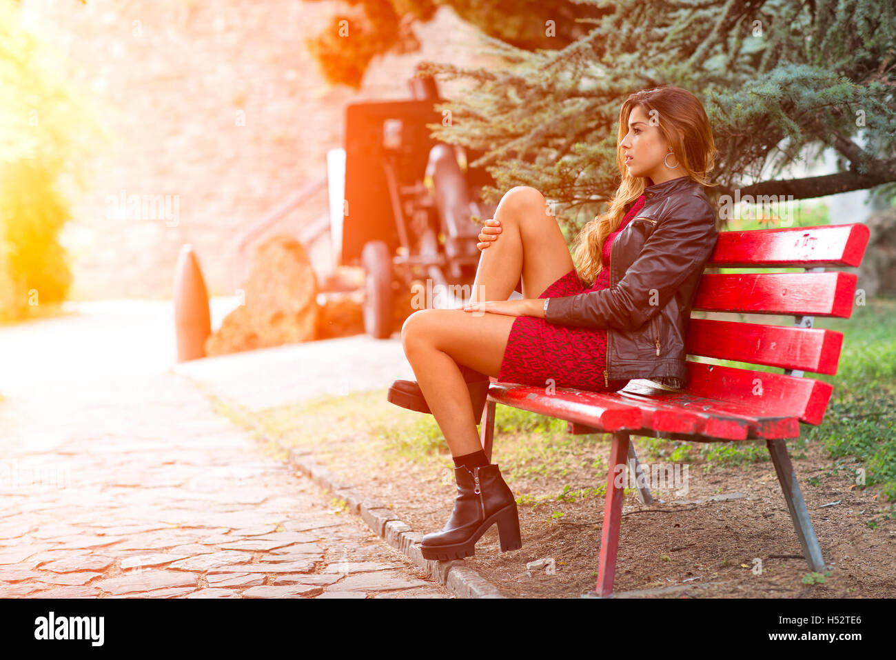 Girl in miniskirt sitting on a red bench - Stock Image