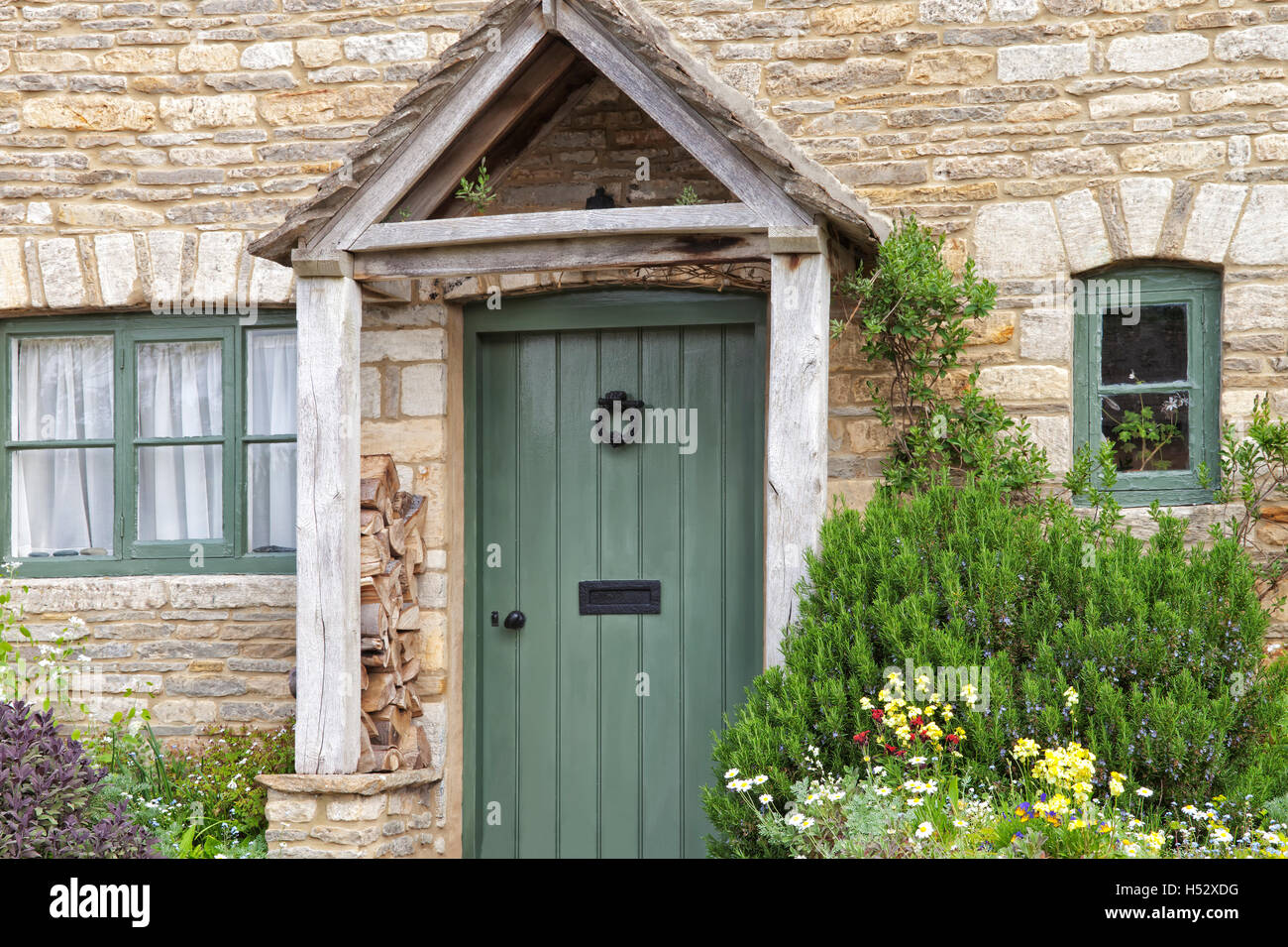 English old stone cottage with green doors wooden entrance canopy and herbs colorful flowers planted in front garden & English old stone cottage with green doors wooden entrance canopy ...