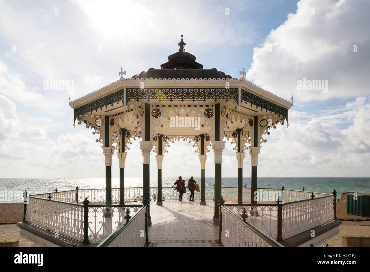 Two people talking in the Victorian bandstand, Brighton seafront, Brighton, East Sussex England UK - Stock Image