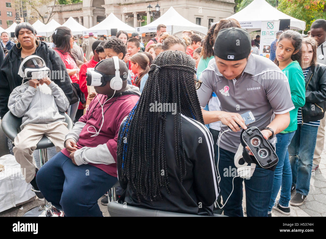 Participants in the Geek Street Fair in Union Square Park in New York experiment with Samsung Oculus VR headsets - Stock Image
