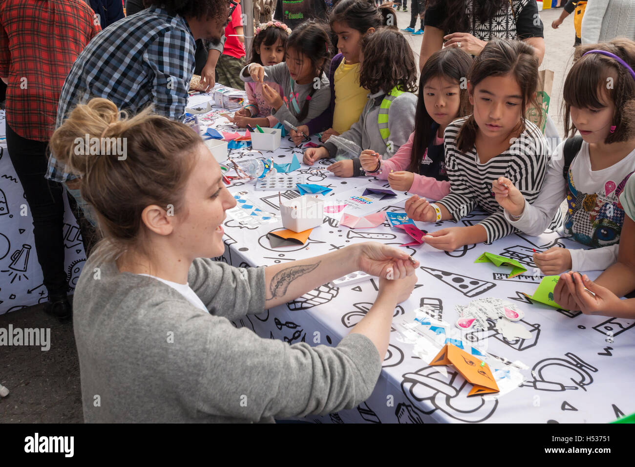 A worker from Blink Blink explains the company's DIY circuitry tools to children at the Geek Street Fair in - Stock Image