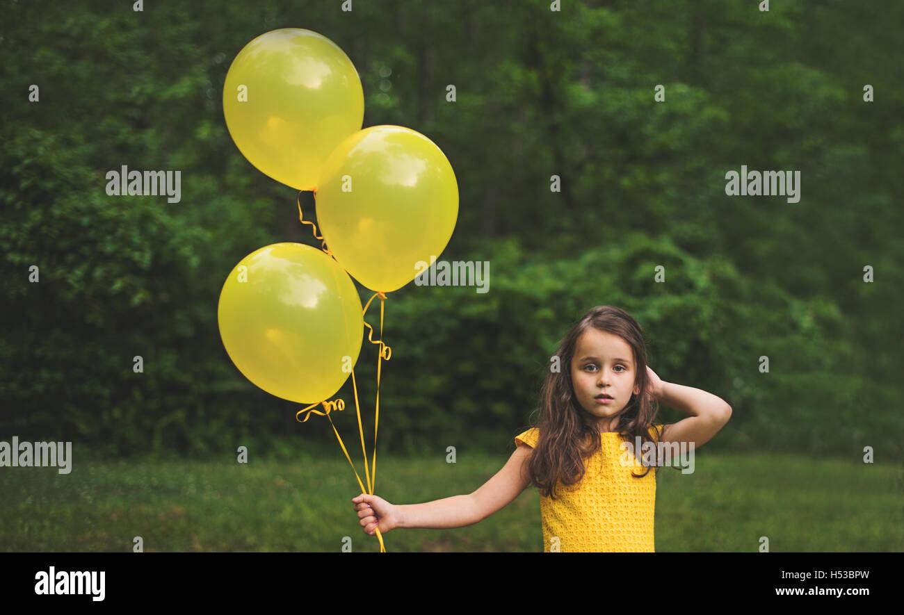 Young girl holding yellow balloons - Stock Image