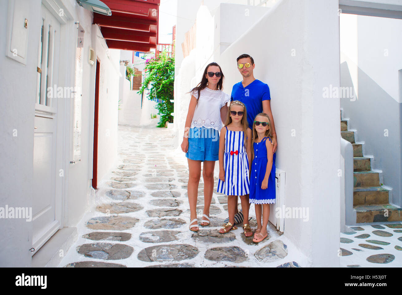 Family Vacation In Europe Parents And Kids At Street Of Typical Greek Traditional Village On Mykonos Island Greece