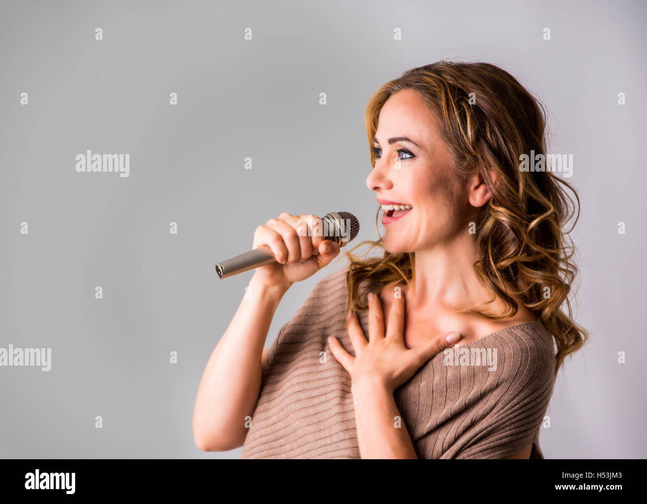 Attractive adult woman speaking into microphone and smile - Stock Image