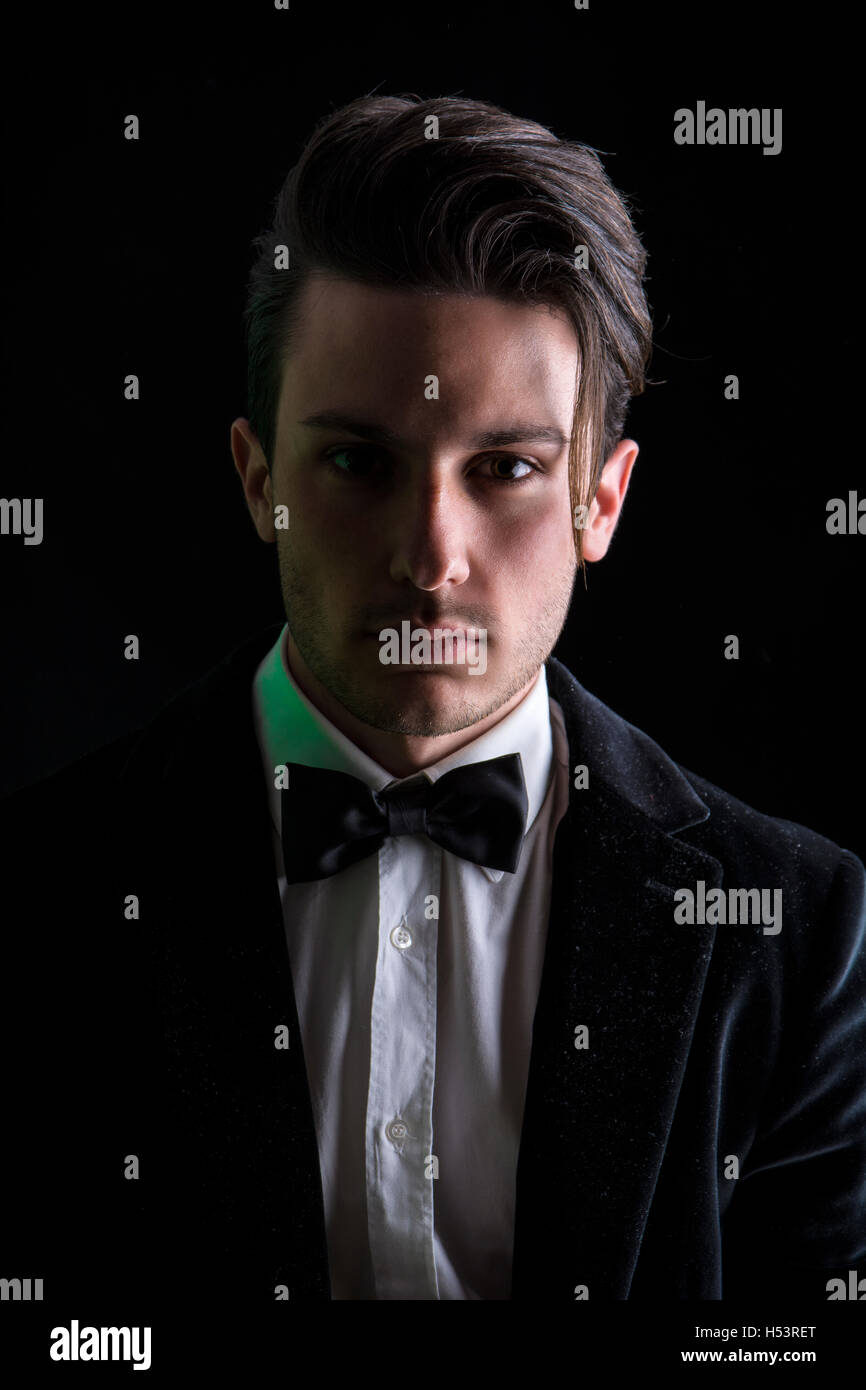Young businessman confidently posing and looking at camera, wearing suit, on dark background Stock Photo