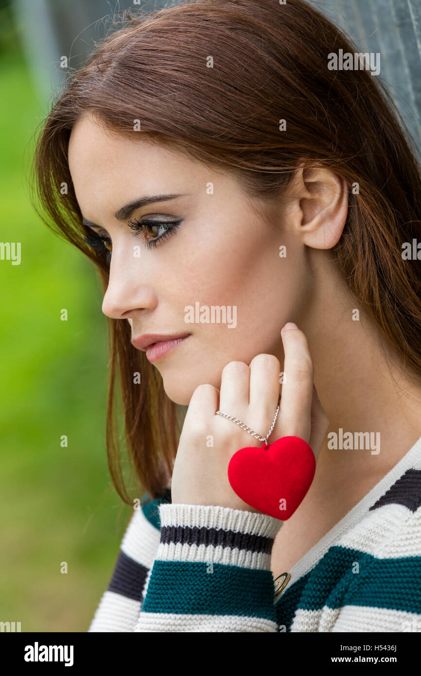 Beautiful thoughtful sad heartbroken girl or young woman with red hair holding a red heart necklace - Stock Image