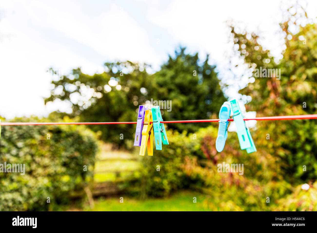 Clothes pegs on washing line clothes peg clipped to washing line for pegging clothing outside to dry air UK England - Stock Image