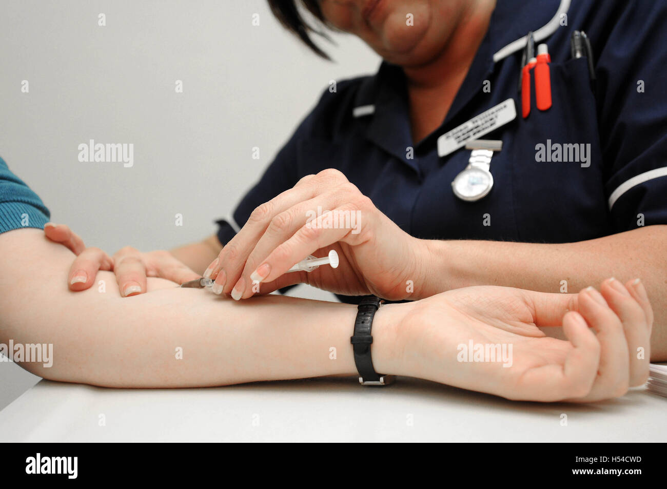A nurse takes blood during a blood test at a doctor's surgery. - Stock Image
