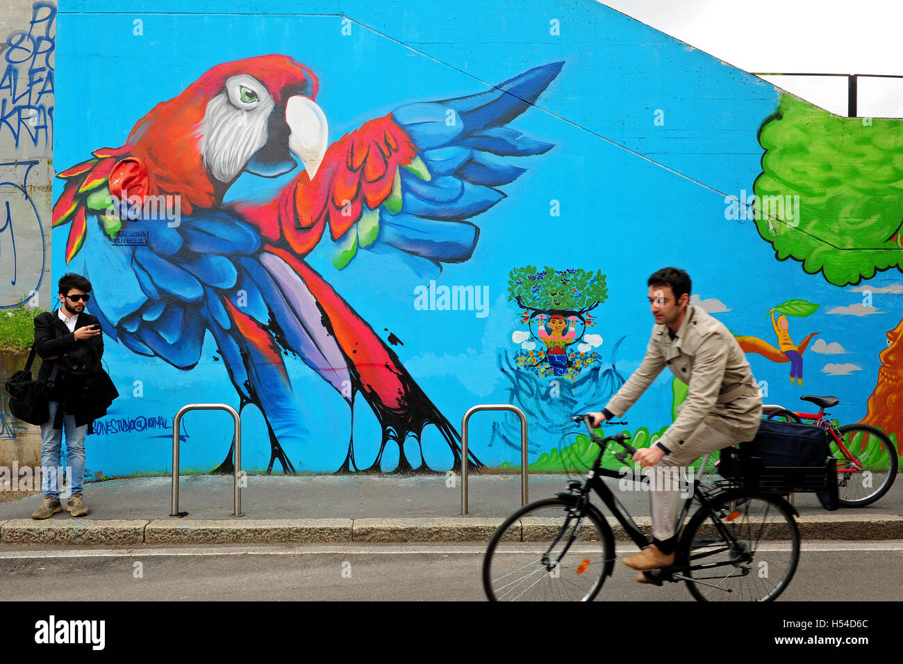 A man on a bicycle rides in front of a giant mural with a parrot, in the Isola district in Milan. Stock Photo