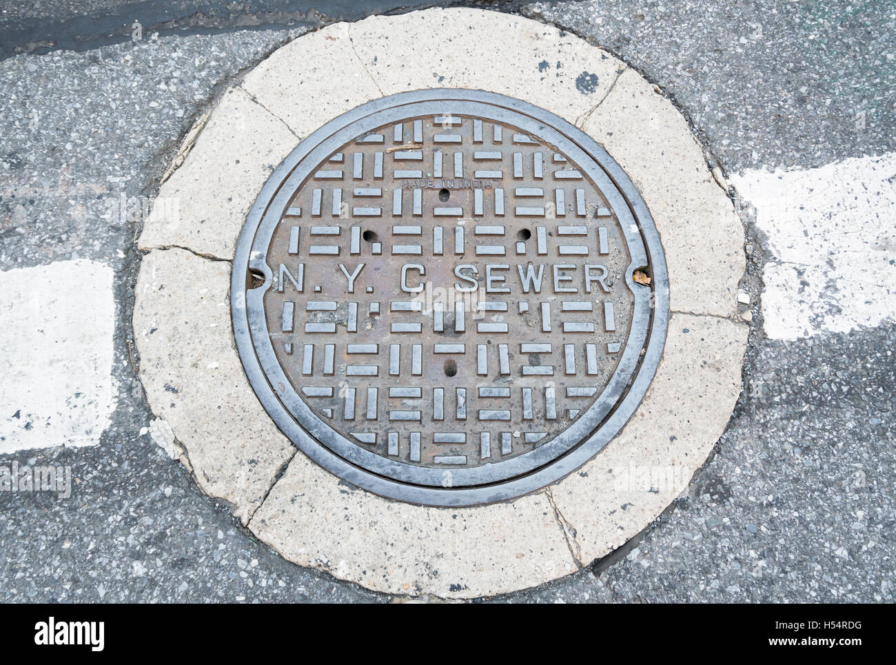 New York City NYC sewer cover / manhole lid in the road - Stock Image